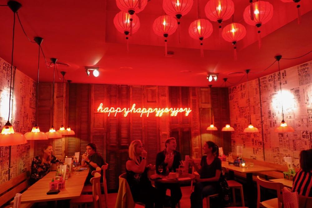 Tafels met gasten bij HappyHappyJoyJoy in het nieuwe filiaal in Amsterdam West.