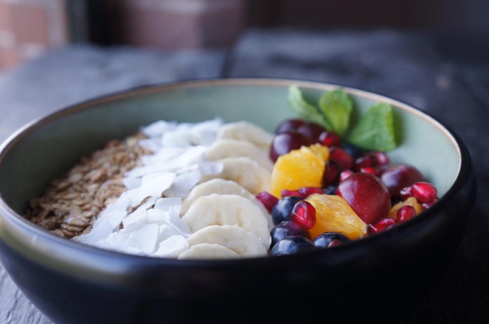 Een zwarte bowl met yoghurt, fruit en granola