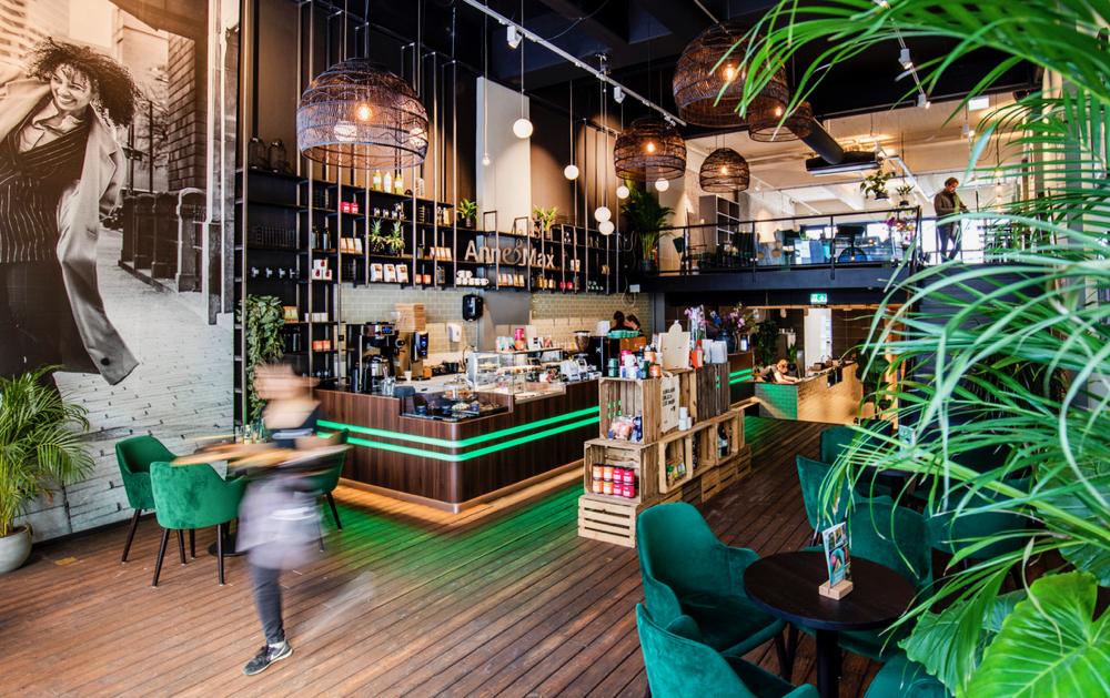 Het interieur van Anne&Max in Rotterdam. Met groen, bruin, hoge wandkasten en veel warmte.