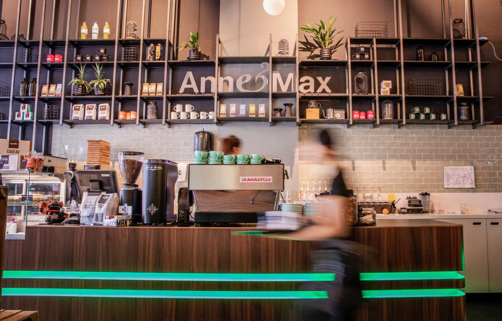 De bar met lichtgevende groene strepen in hout en een grote wandkast erachter