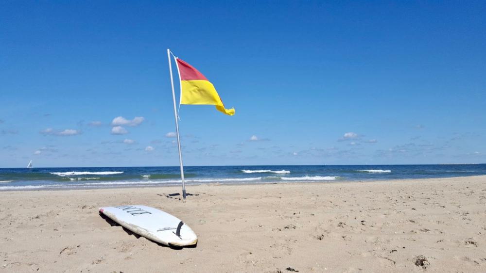 Een surfplank met een vlag op het strand van Vlieland