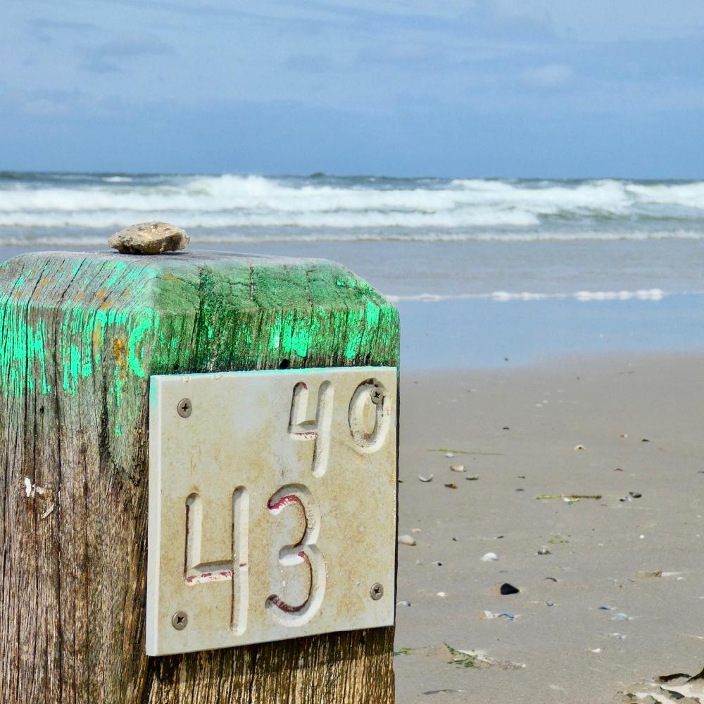 Een paal op het strand, met een groene bovenkant. De branding op de achtergrond.
