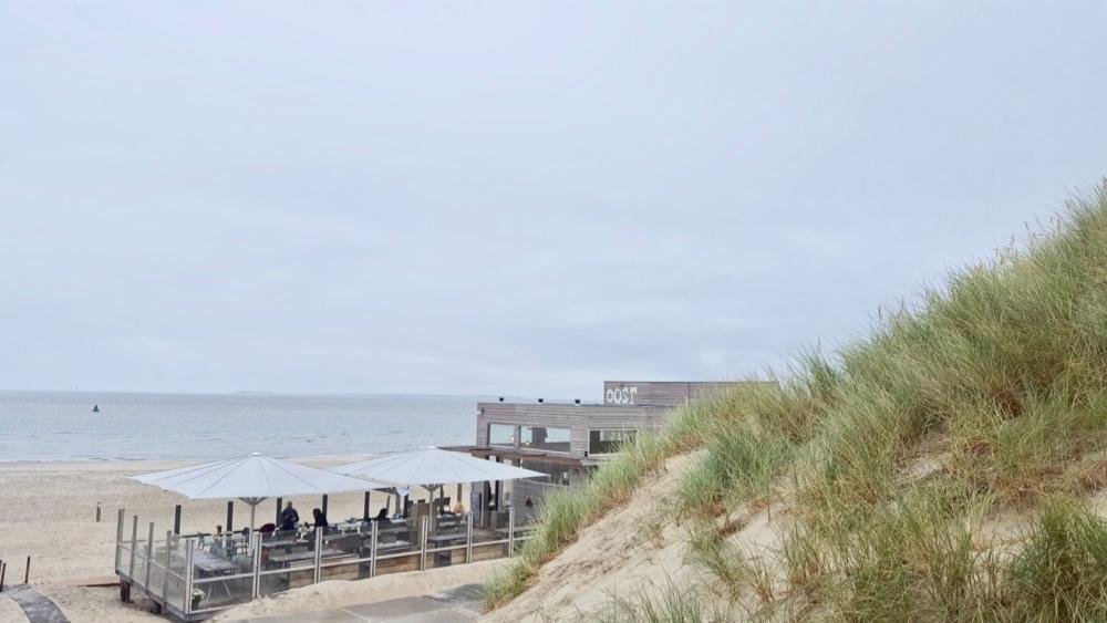 De achterkant van Strandtent Oost Vlieland met duinen en de zee