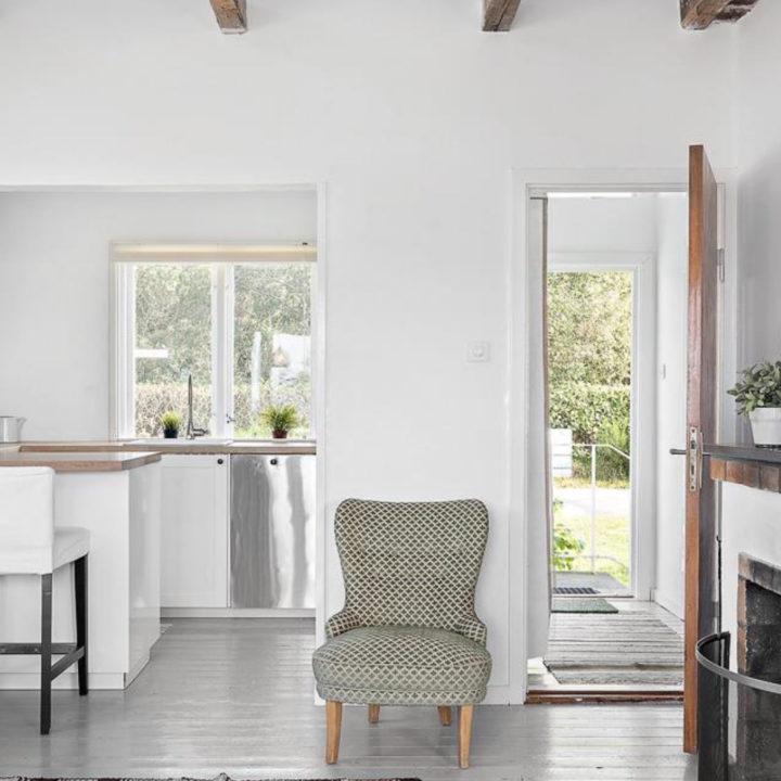Wit huis met kleine fauteuil, buitendeur staat open