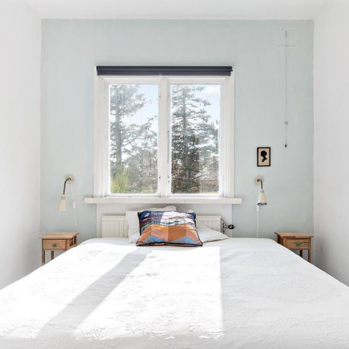 Tweepersoons kamer met witte sprei, zonlicht valt op het bed