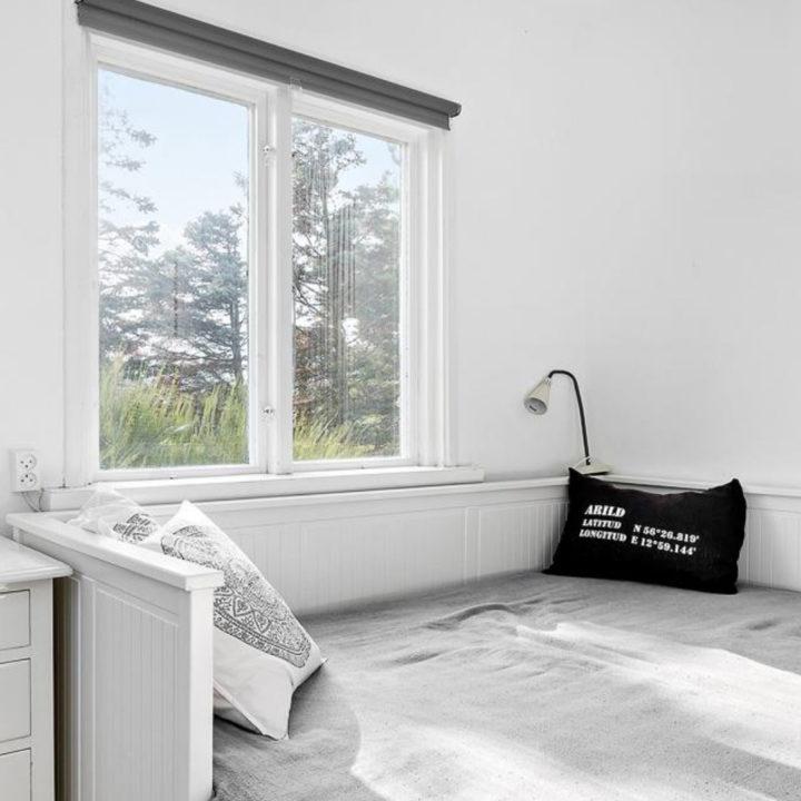 Lichte kamer met bed voor het raam met kussens erop.