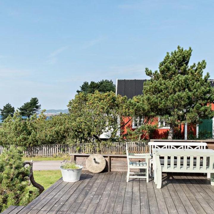 Veranda met houten banken en een rood houten buurhuis