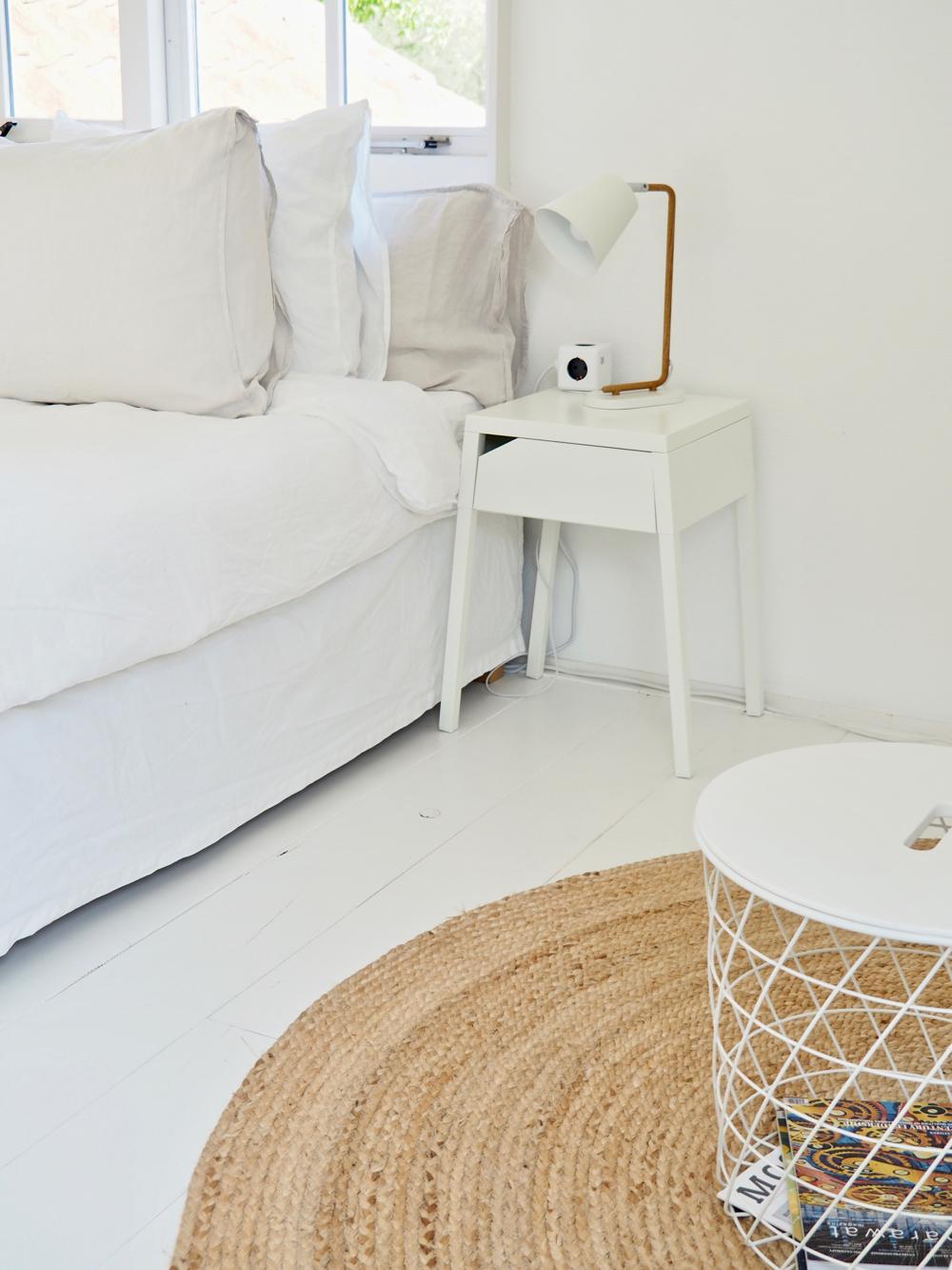 Slaapkamer in alle tinten wit. Wit bed met wit nachtkastje en wit tafeltje.