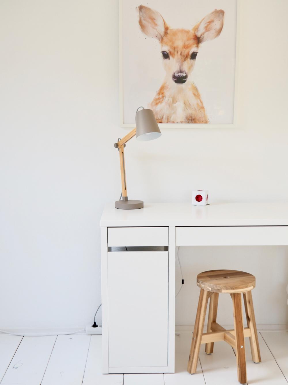 Een wit bureautje met houten krukje en afbeelding van hertje