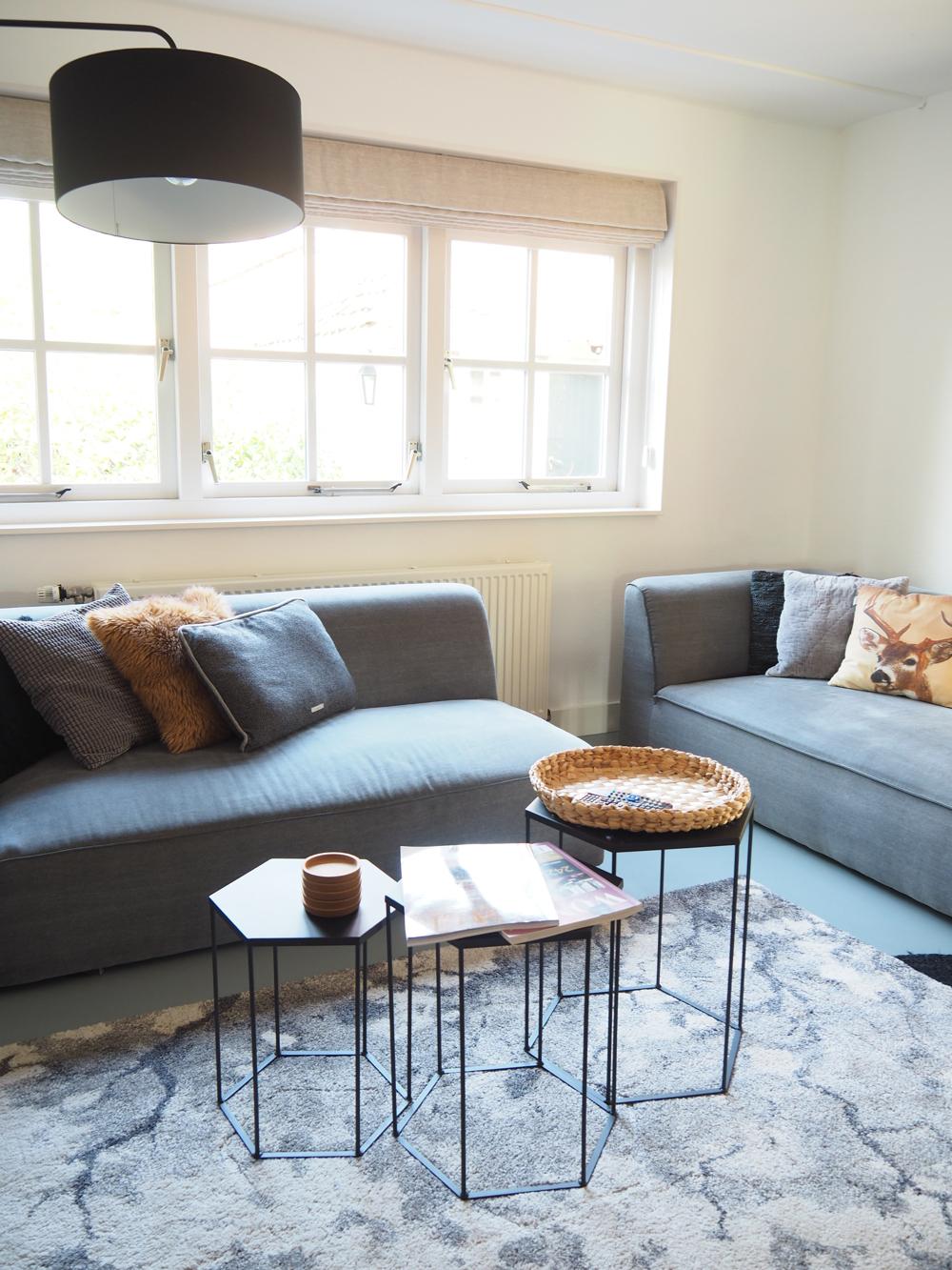 Woonkamer met twee grijze banken, kleine salontafels en een kleed, in Scandinavische sfeer.