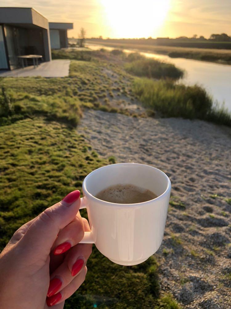 Een kopje koffie met opkomende zon