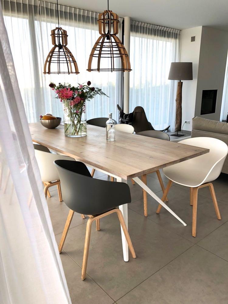 Een grote eettafel met 8 kuipstoelen in zwart en wit in de Z'AND villa