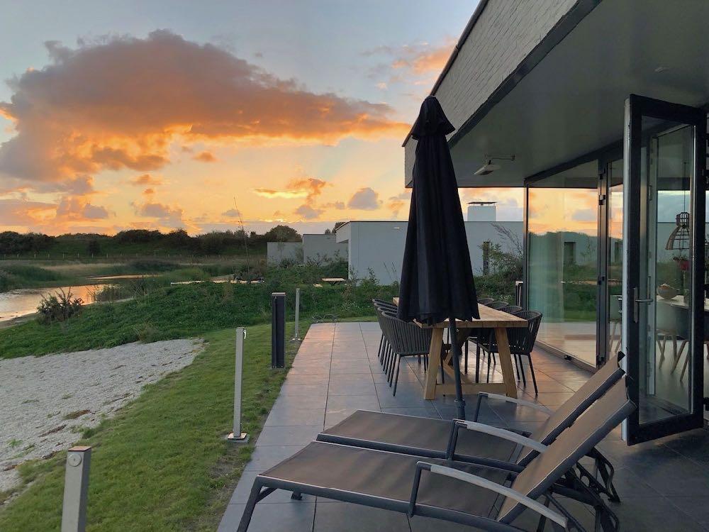 Vanaf het terras van de Z'ANDvilla kijk je uit over de polders en prachtige wolkenluchten