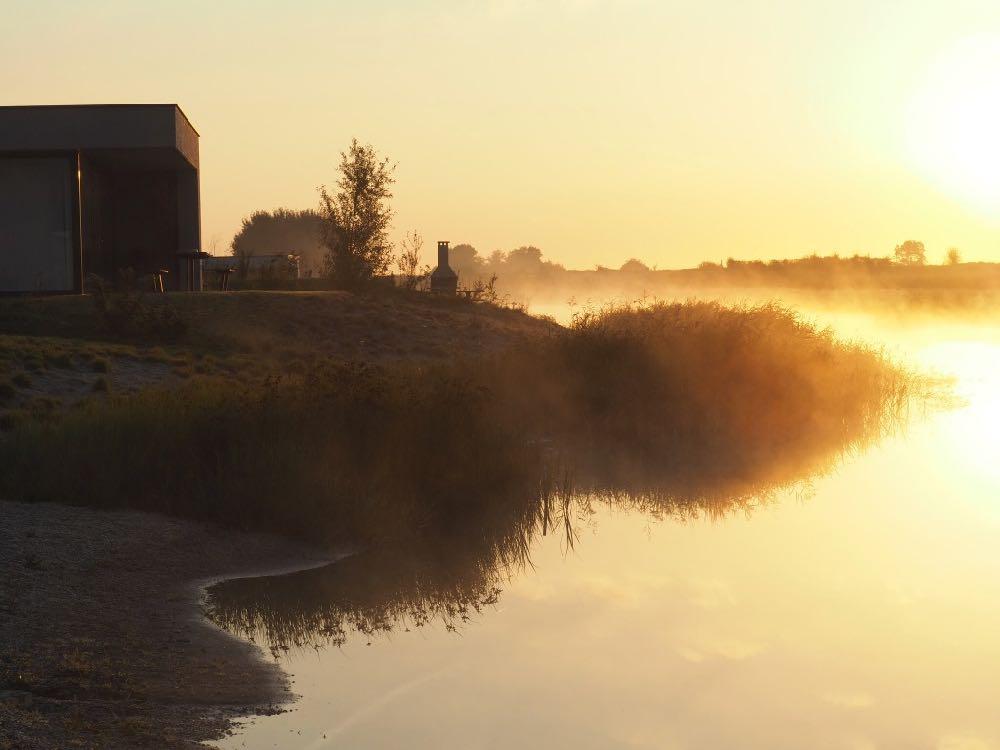 De zon komt op boven het water bij de zonsopgang Z'AND villa's