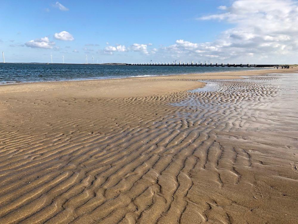 Strand met in de verte de Deltawerken