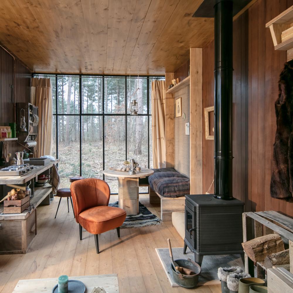 Het interieur van een Nutchel Cosy Cabin met veel houtwerk, een houtkachel en gezellig zitje
