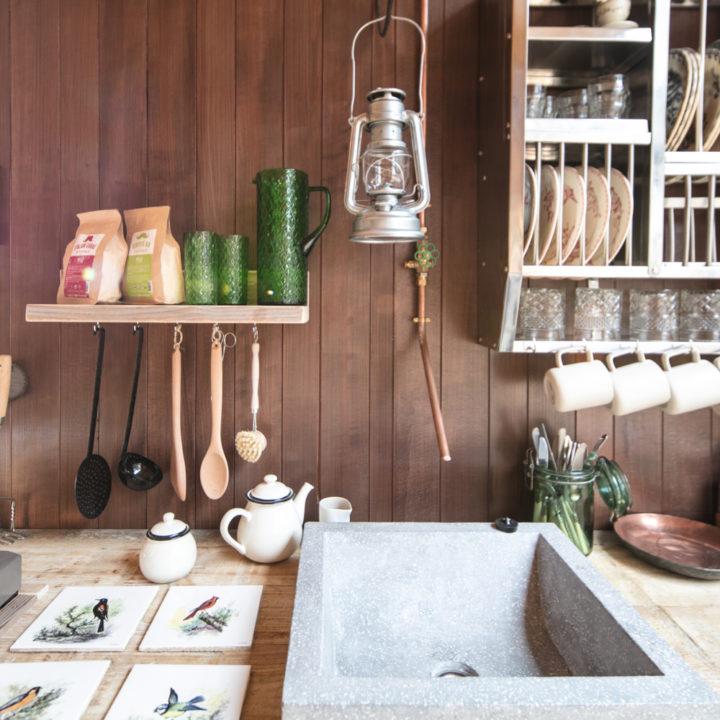 Close up van een keuken in de Nutchel Cosy Cabin, met olielamp, afwasborstel en theepotje