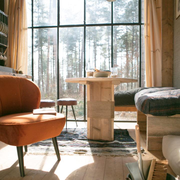 Fauteuil en zithoek in het zonlicht, voor de grote stalen ramen.