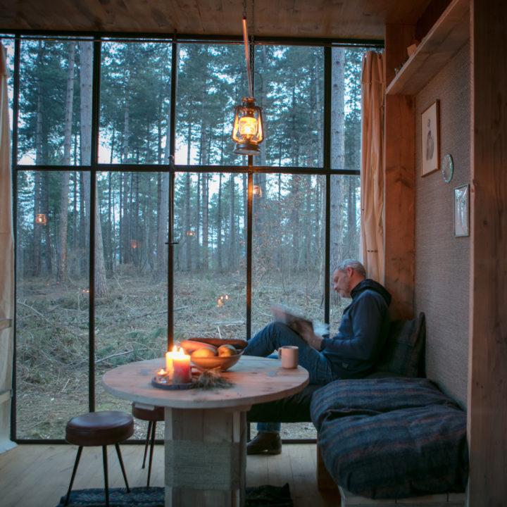 Een boek lezen in de Nutchel Cosy Cabin, bij de grote stalen ramen in de schemering bij kaarslicht