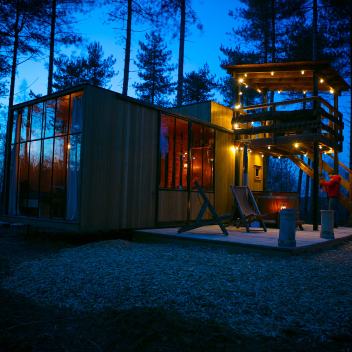 Een van de grotere cabins in de avond, met sfeerverlichting buiten.