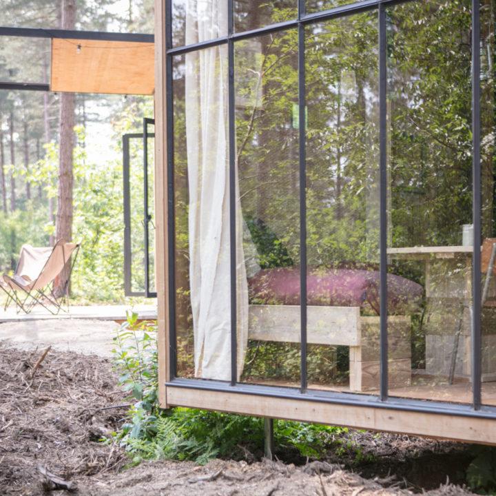 Doorkijkje van buiten naar binnen en een terrasje met twee vlinderstoelen op de achtergrond.