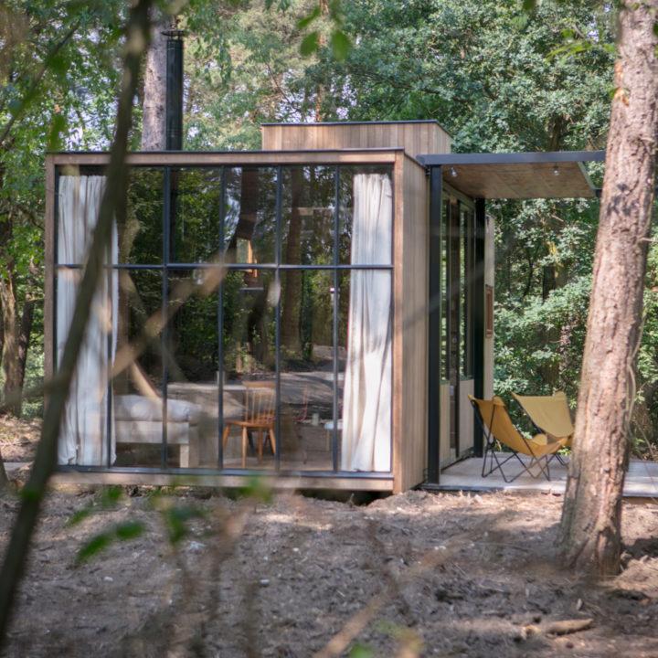 Cabin van buiten. Grote stalen ramen met uitzicht op het bos