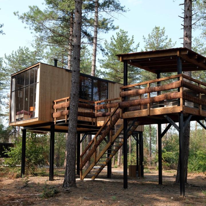 Een tiny house op palen, met groot terras op palen. Tussen de bomen.