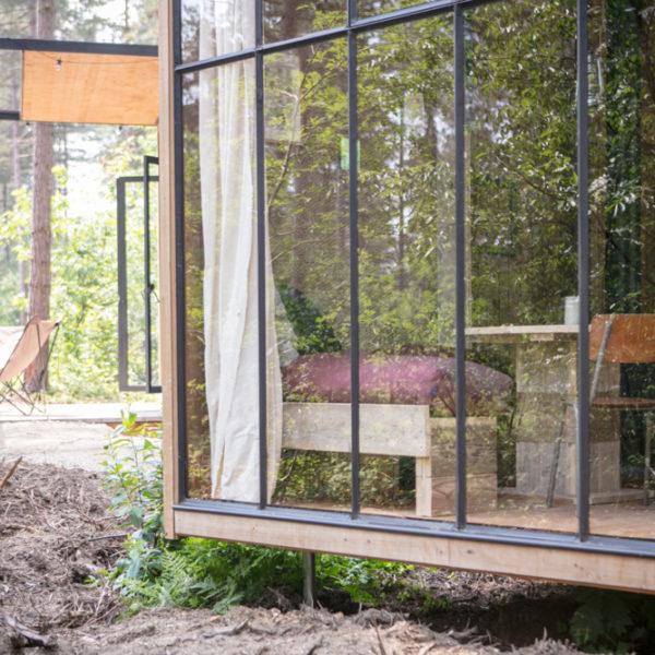 Buiten aanzicht van een Natuurhuisje, een Cosy Cabin met grote stalen ramen en een terras met twee vlinderstoelen. In het bos.