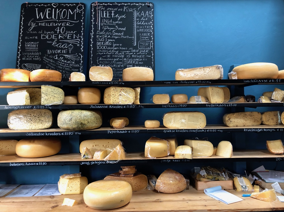 De toonbank in de kaaswinkel met planken met kaas en een blauwe achterwand
