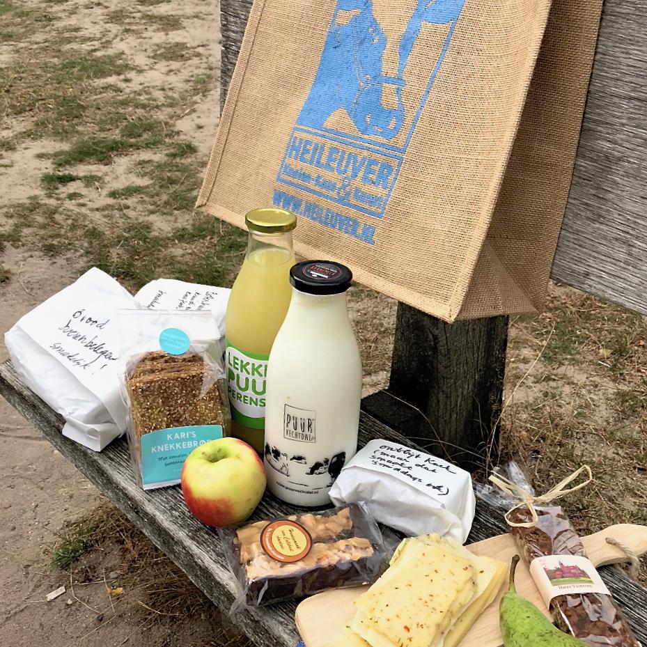 Picknick op een bankje, met verse melk en sap, brood, kaas, appels en lekkere crackers.