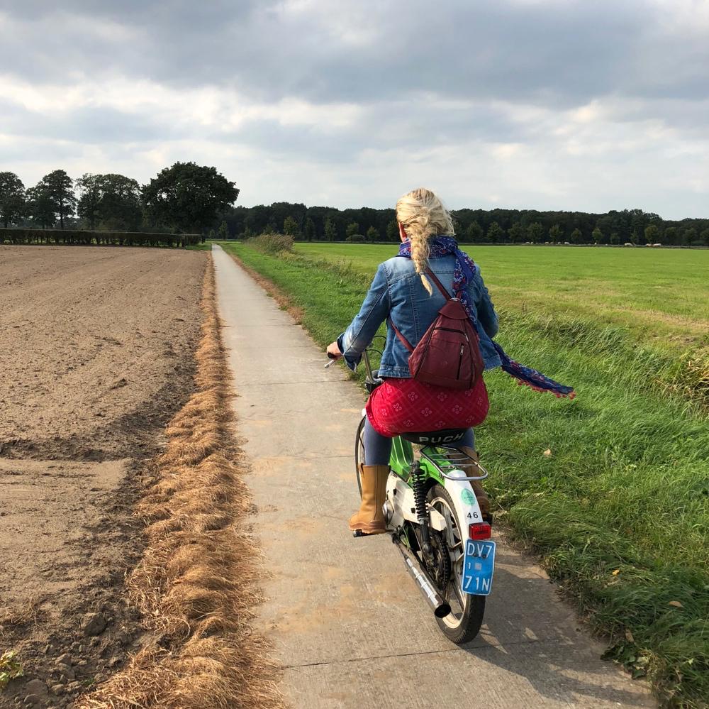Toffe Puch met dame met lange blonde vlecht op een fietspaadje door de weilanden