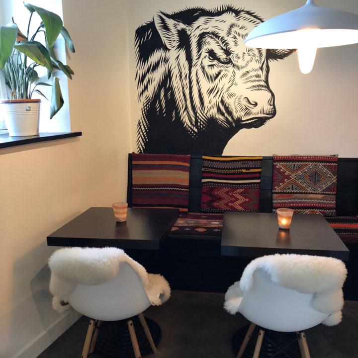 Zwarte tafels, een muurbank en witte kuipstoelen