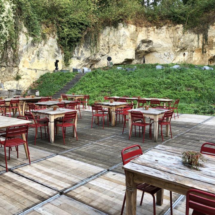 Rode metalen stoelen en houten tafels aan de voet van de mergelwand