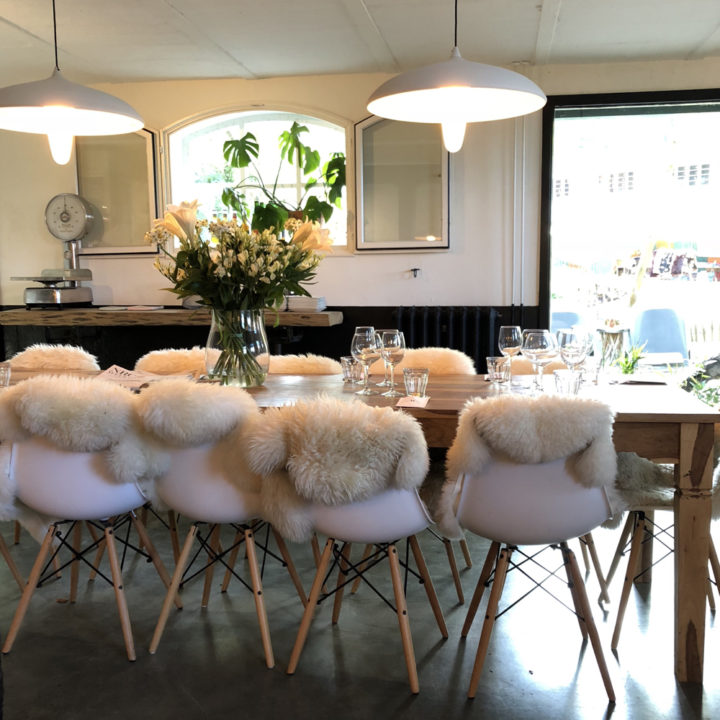 lange tafel met witte stoelen en bontjes erop