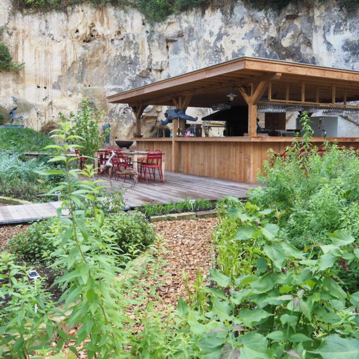 Een bar tegen een mergelwand, met rode stoelen op het terras met houten vlonders.