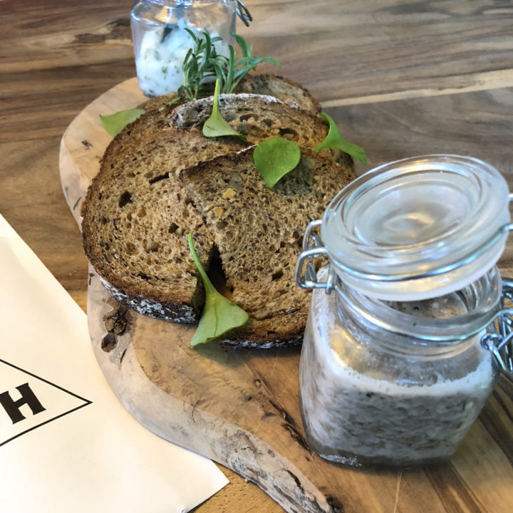 Grof brood op een plank, met huisgemaakte kruidenboter en zure zult.