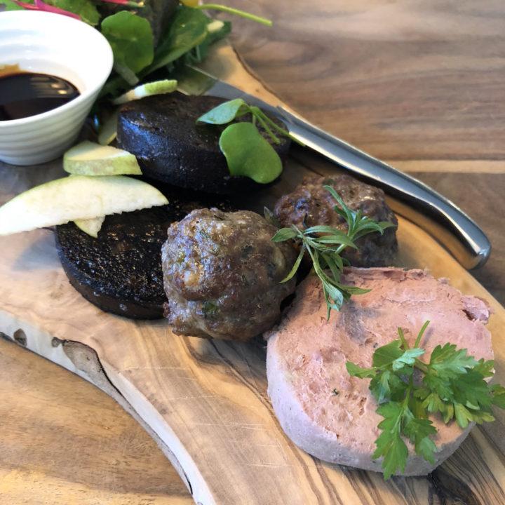 Een trio van varkensvlees, met bloedworst, gehaktbal en paté op een plank.