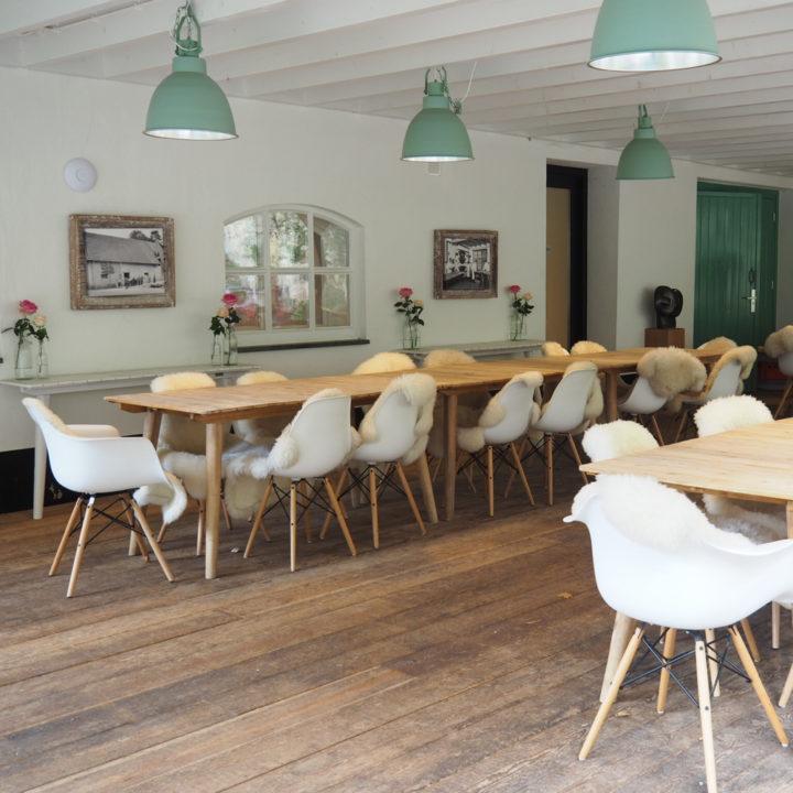 Lange houten tafels met witte stoelen met vachtjes op de veranda van de Heerdeberg