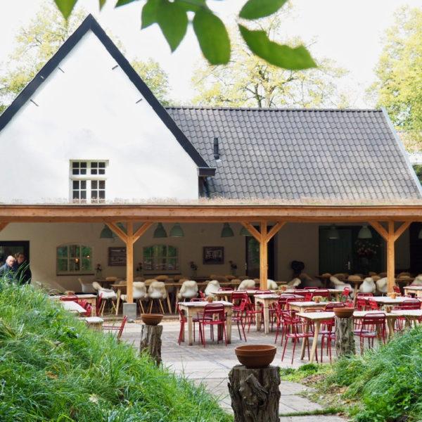 De Heerdeberg vanuit de tuin, met rode stoelen op het terras, een veranda met lange tafels.