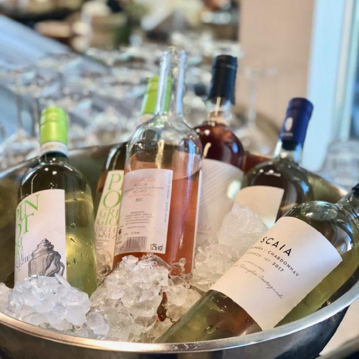 Een schaal met ijsblokjes en daarin flessen wijn