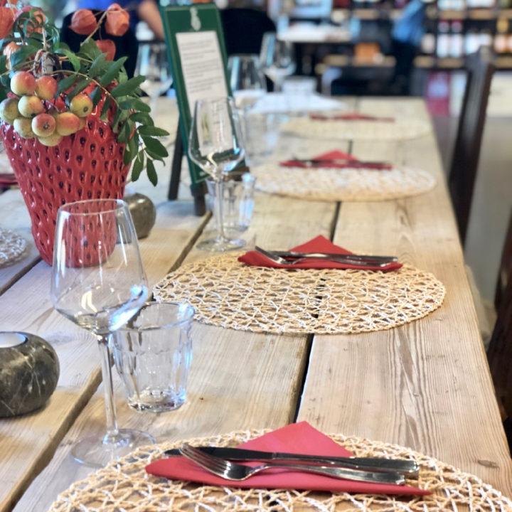 Een stoeren houten tafel met placemates, rode servetten en wijnglazen