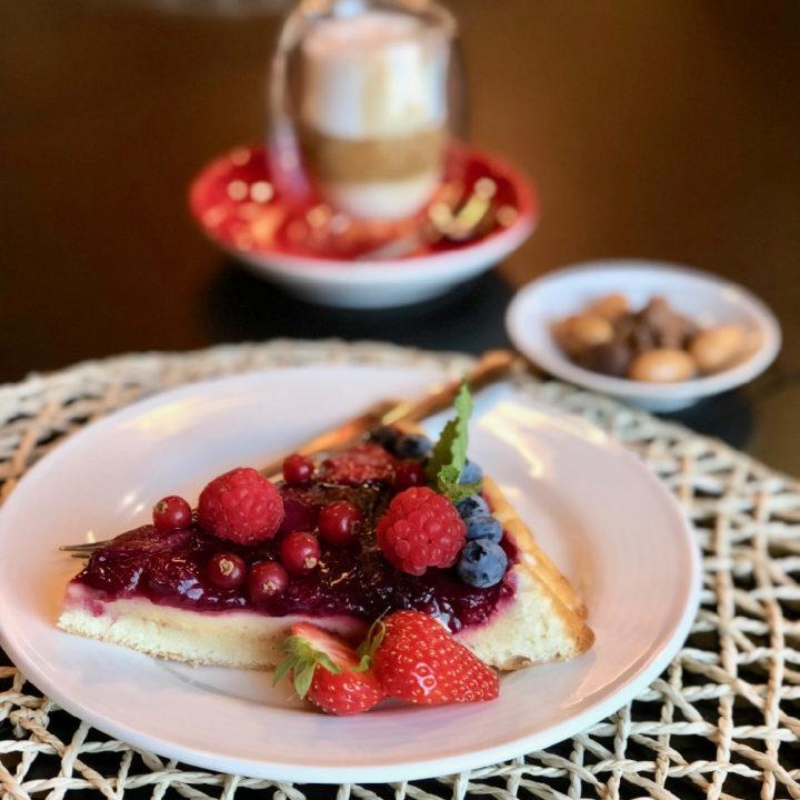 Een taart met rood fruit en een cappuccino