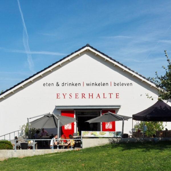 Vooraanzicht van lunchwinkel en delicatessenzaak de Eyserhalte. Een witte gevel met rode deuren en terras ervoor.