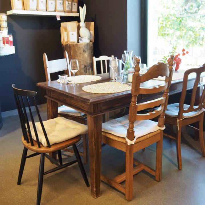 Een tafel voor het raam met verschillende stoelen