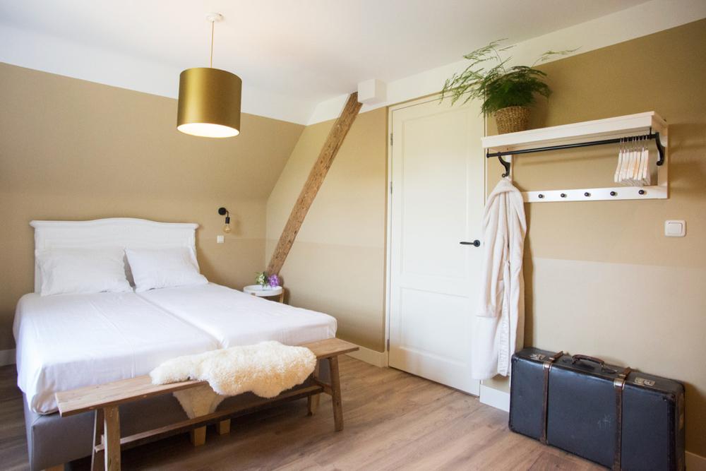 Slaapkamer met tweepersoonsbed met wit linnengoed en zachte tinten op de wand