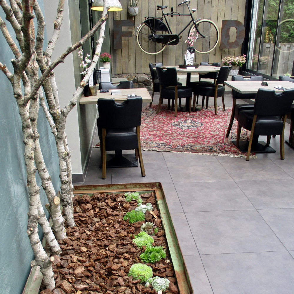 Restaurant Maes 21 met tafeltjes in de serre en een fiets aan de muur