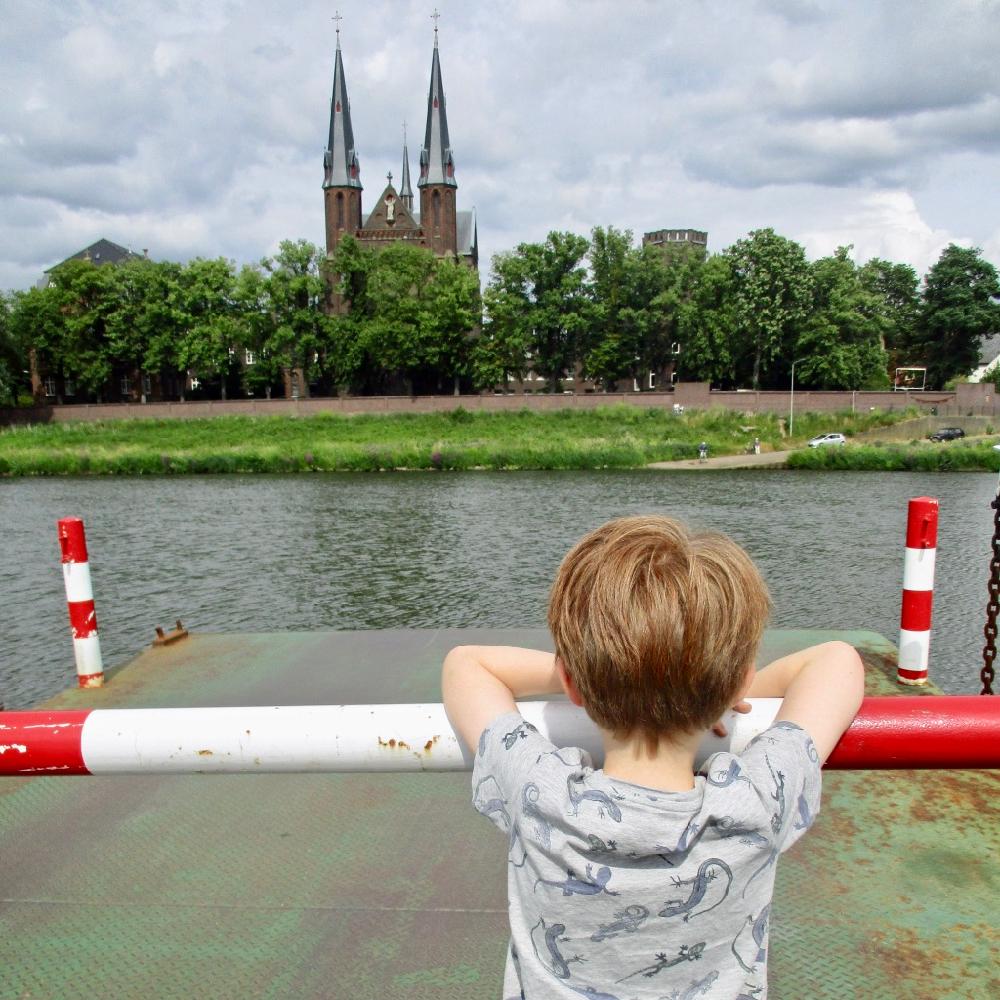 Een jongetje leunt op de slagboom van een pontje en kijkt naar de overkant van het water.