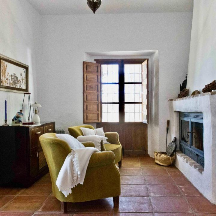 Twee fauteuils voor de haard van een van de vakantiehuizen van Cortijo Juan Salvador