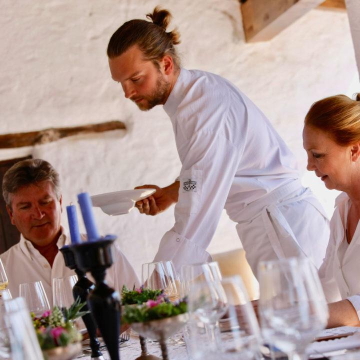 Het eten wordt opgediend aan tafel met glazen en mooi servies.