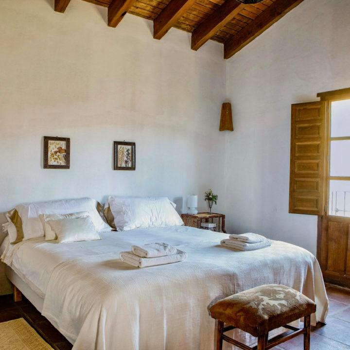 Slaapkamer met tweepersoons bed en authentieke houten balken